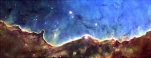 """This """"landmark"""" image from the cosmos celebrated the 10th anniversary of the Hubble Space Telescope's Hubble Heritage Project. Cutting across a nearby star-forming region, called NGC 3324, are the """"hills and valleys"""" of gas and dust displayed in intricate detail. Set amid a backdrop of soft, glowing blue light are wispy tendrils of gas as well as dark trunks of dust that are light-years in height. NGC 3324 is located in the constellation Carina, about 7,200 light-years away from Earth."""